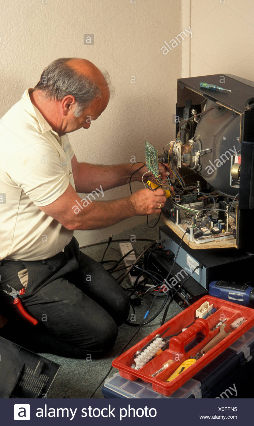 man repairing or taking an old analogue television to pieces - Stock Image