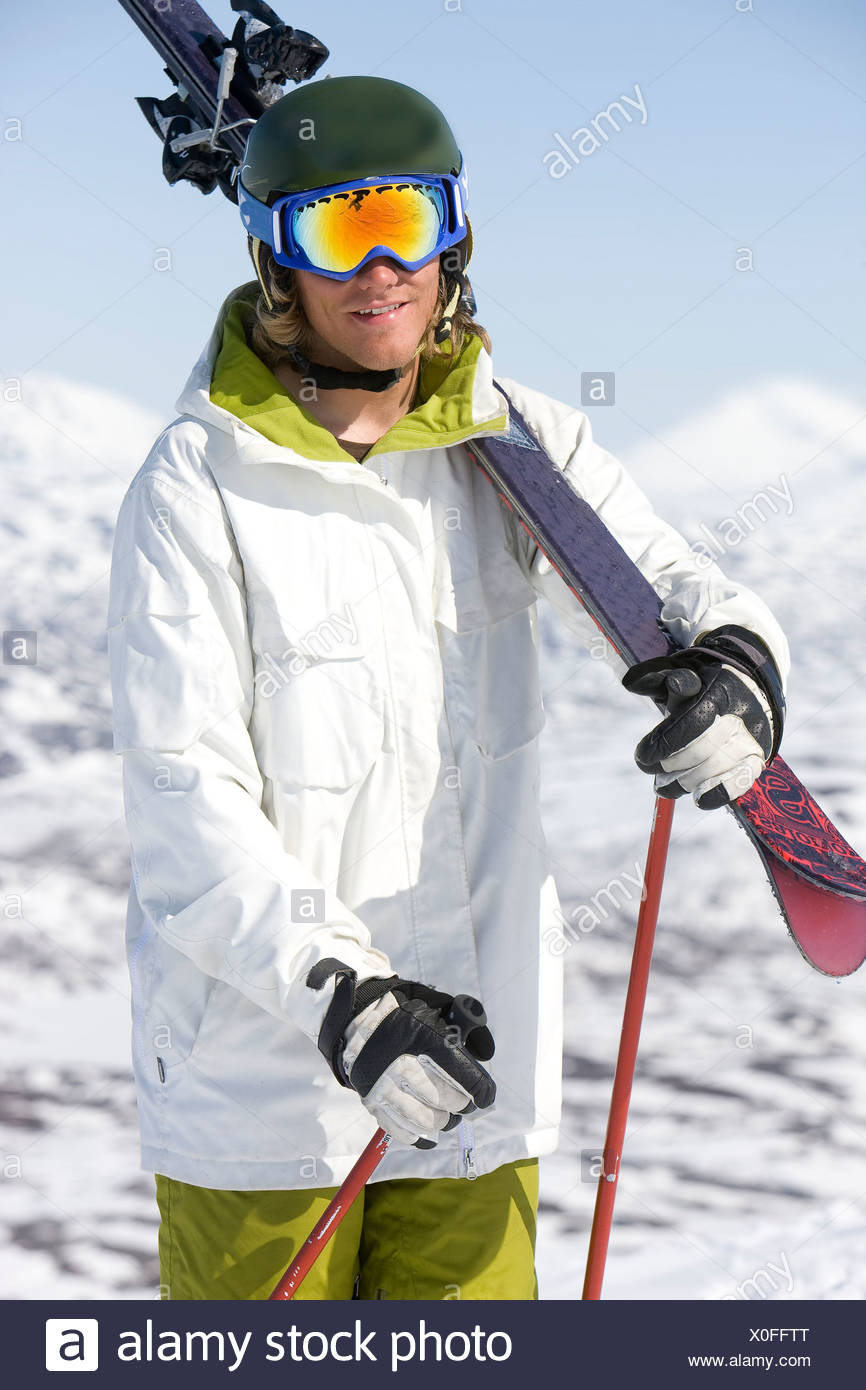 Portrait of a male skier with ski goggles and ski on shoulder - Stock Image