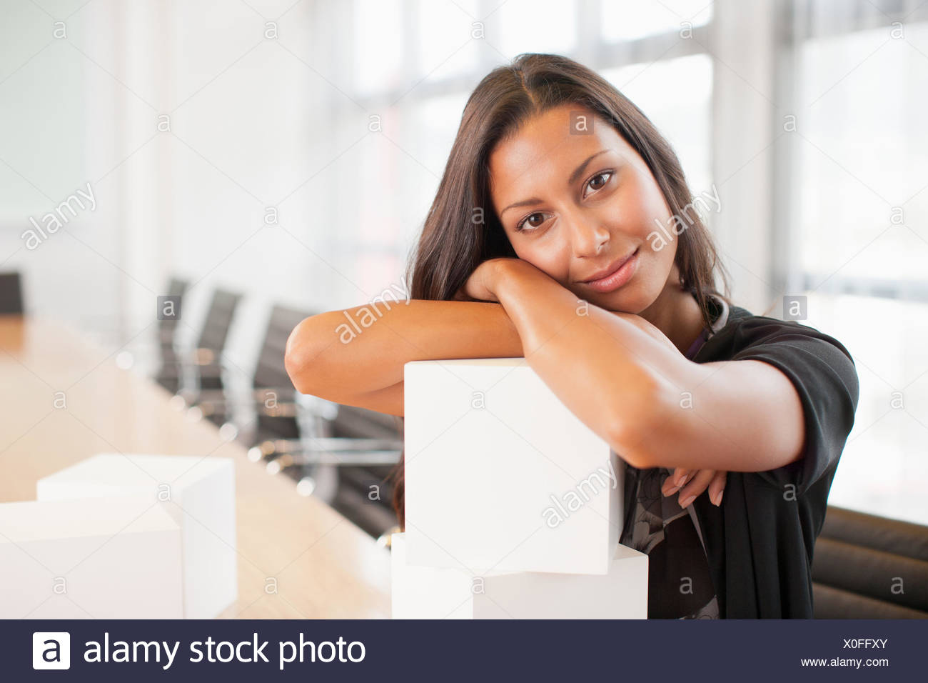 Businesswoman sitting in conference room with white cubes - Stock Image