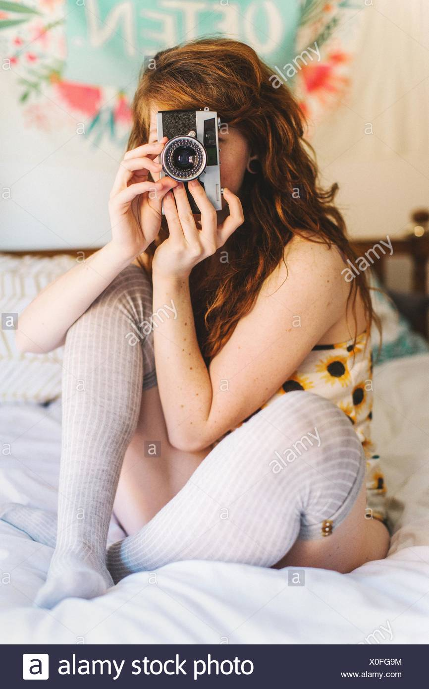 Young woman sitting on bed, looking through SLR camera - Stock Image