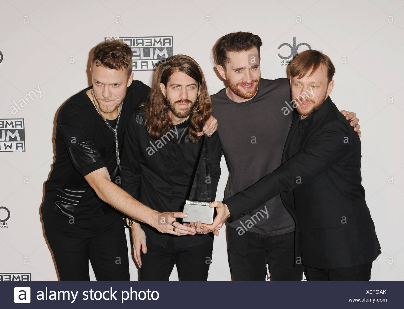 (L-R) Musicians Ben McKee, Daniel Platzman, Daniel Wayne Sermon and Dan Reynolds of Imagine Dragons pose in the press room at the 2014 American Music Awards at Nokia Theatre L.A. Live on November 23, 2014 in Los Angeles, California., Additional-Rights-Clearances-NA - Stock Image