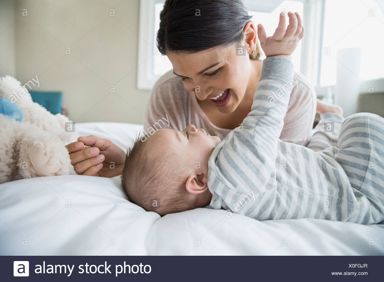 Mother and baby laughing on bed - Stock Image