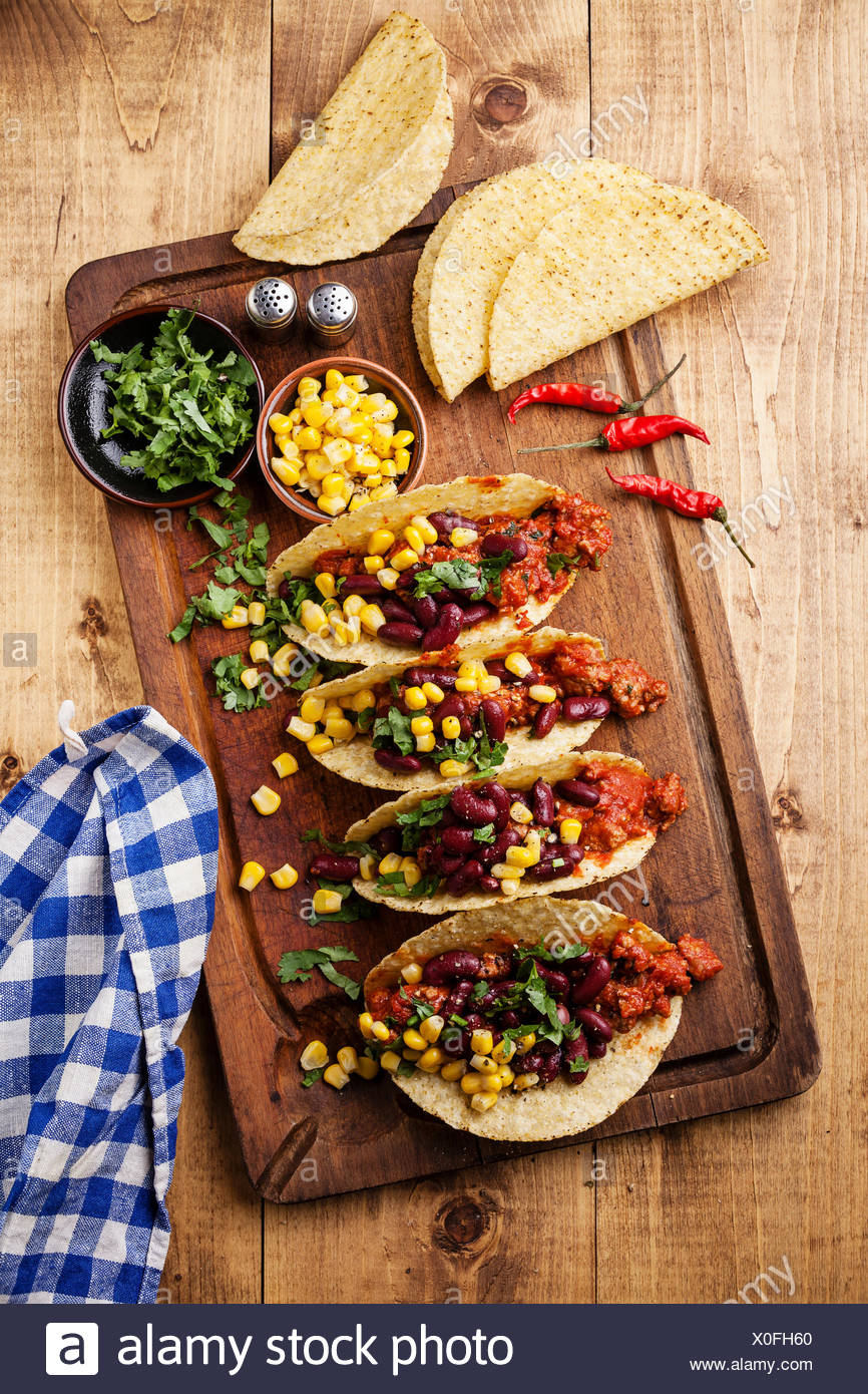 Tacos with ground beef, corn and red beans on wooden table - Stock Image