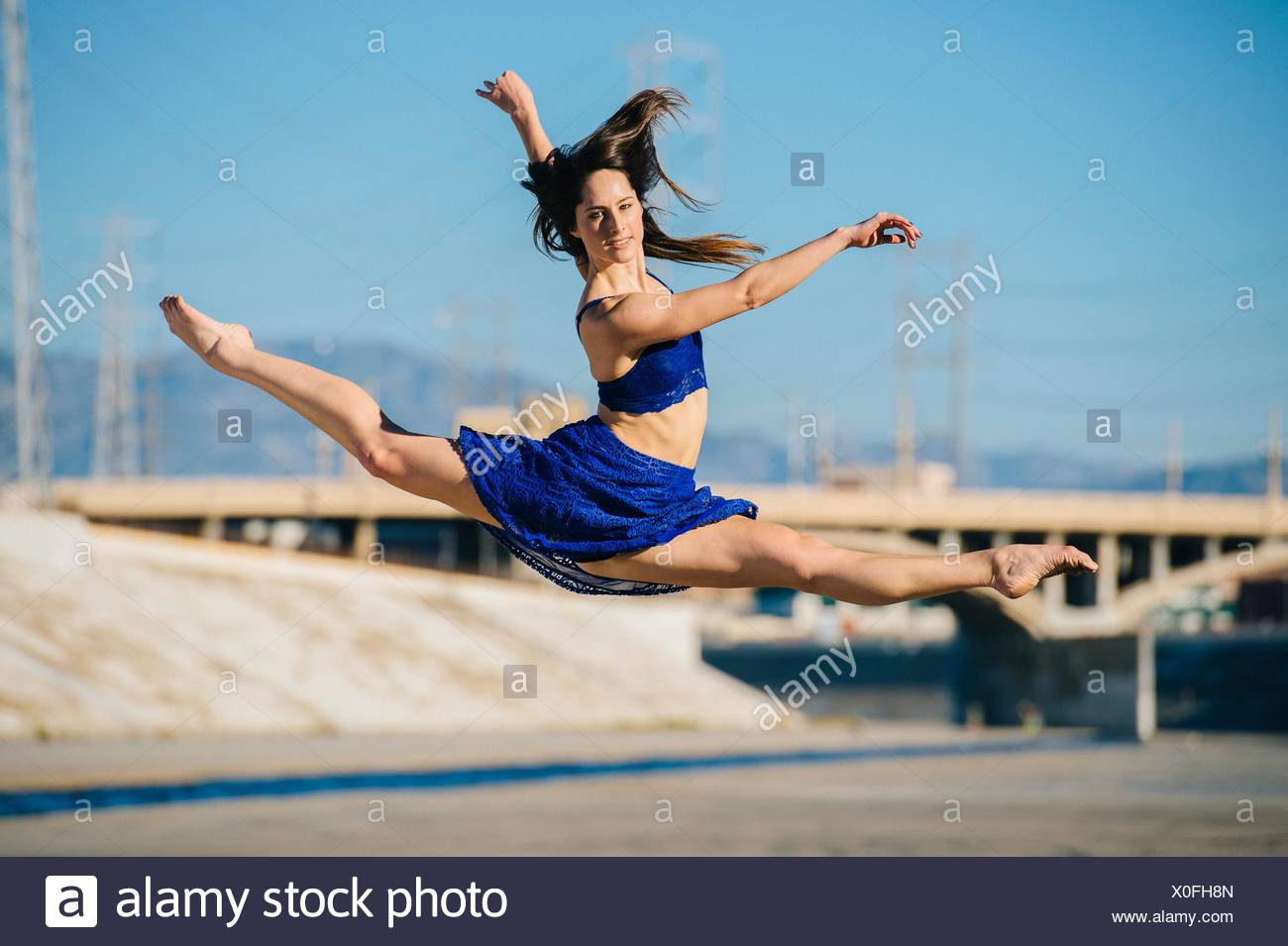Side view of young woman doing the splits in mid air looking at camera smiling, Los Angeles, California, USA - Stock Image