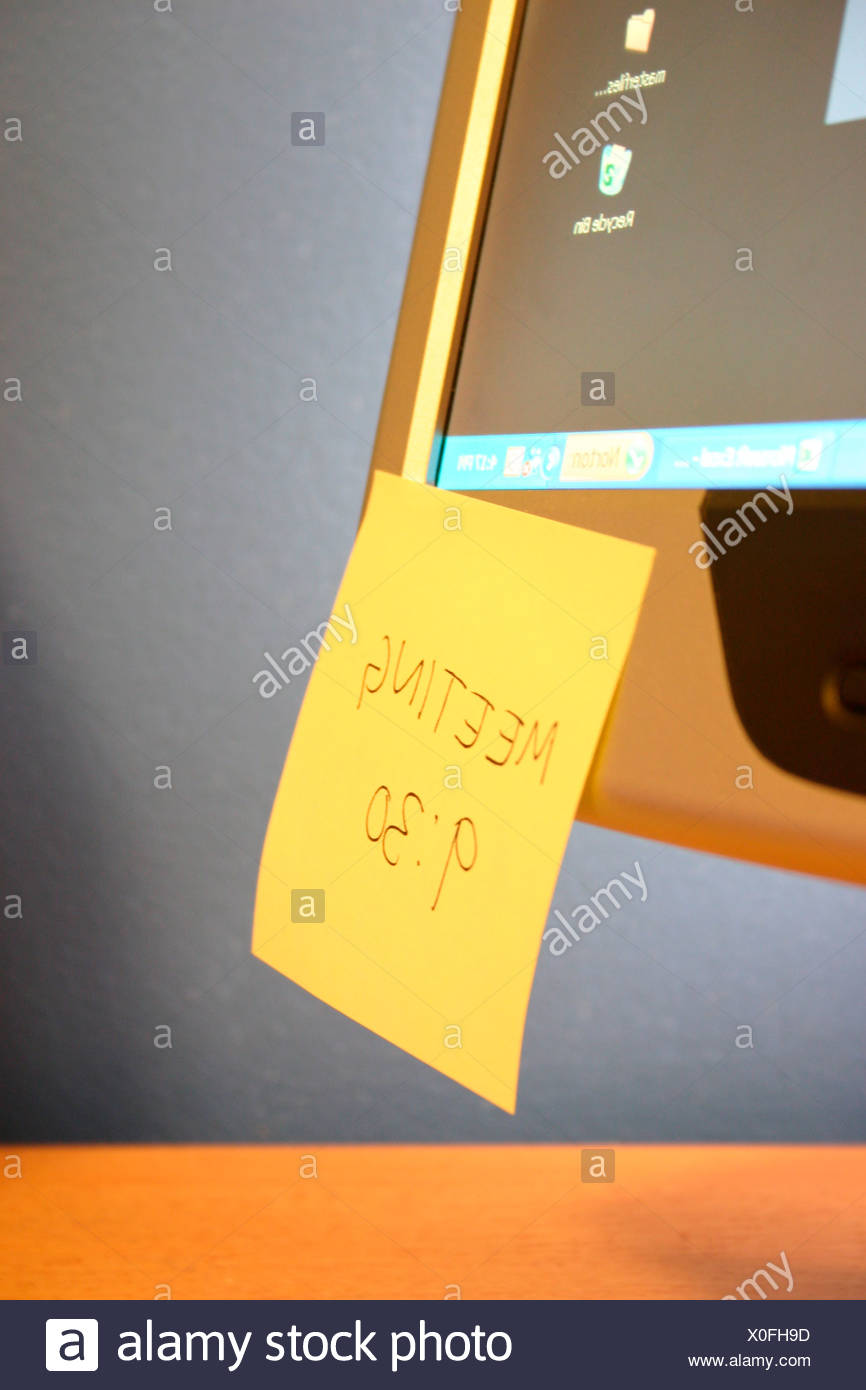 Meeting reminder stuck on computer monitor, close-up - Stock Image