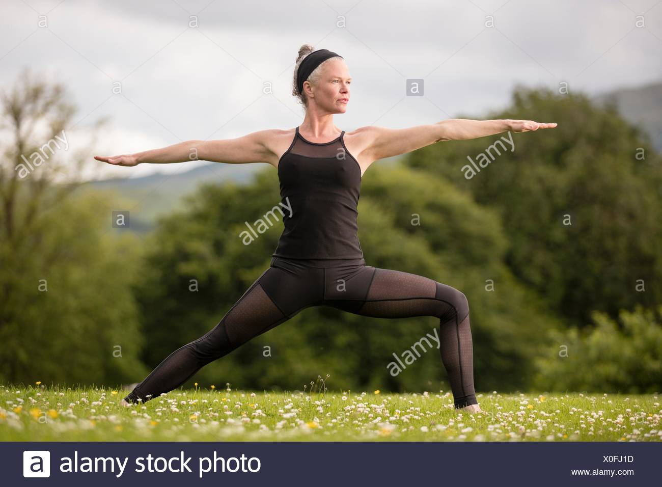 Mature woman practicing yoga reversed warrior pose with arms open in field - Stock Image