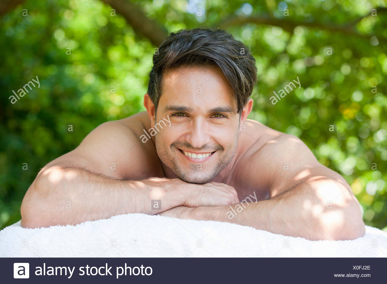 Portrait happy brunette man laying on massage table under tree - Stock Image