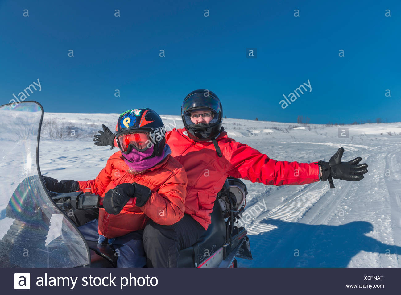 Woman and young girl Snow Machining, Winter, Petersville, Southcentral Alaska, Alaska, USA. - Stock Image