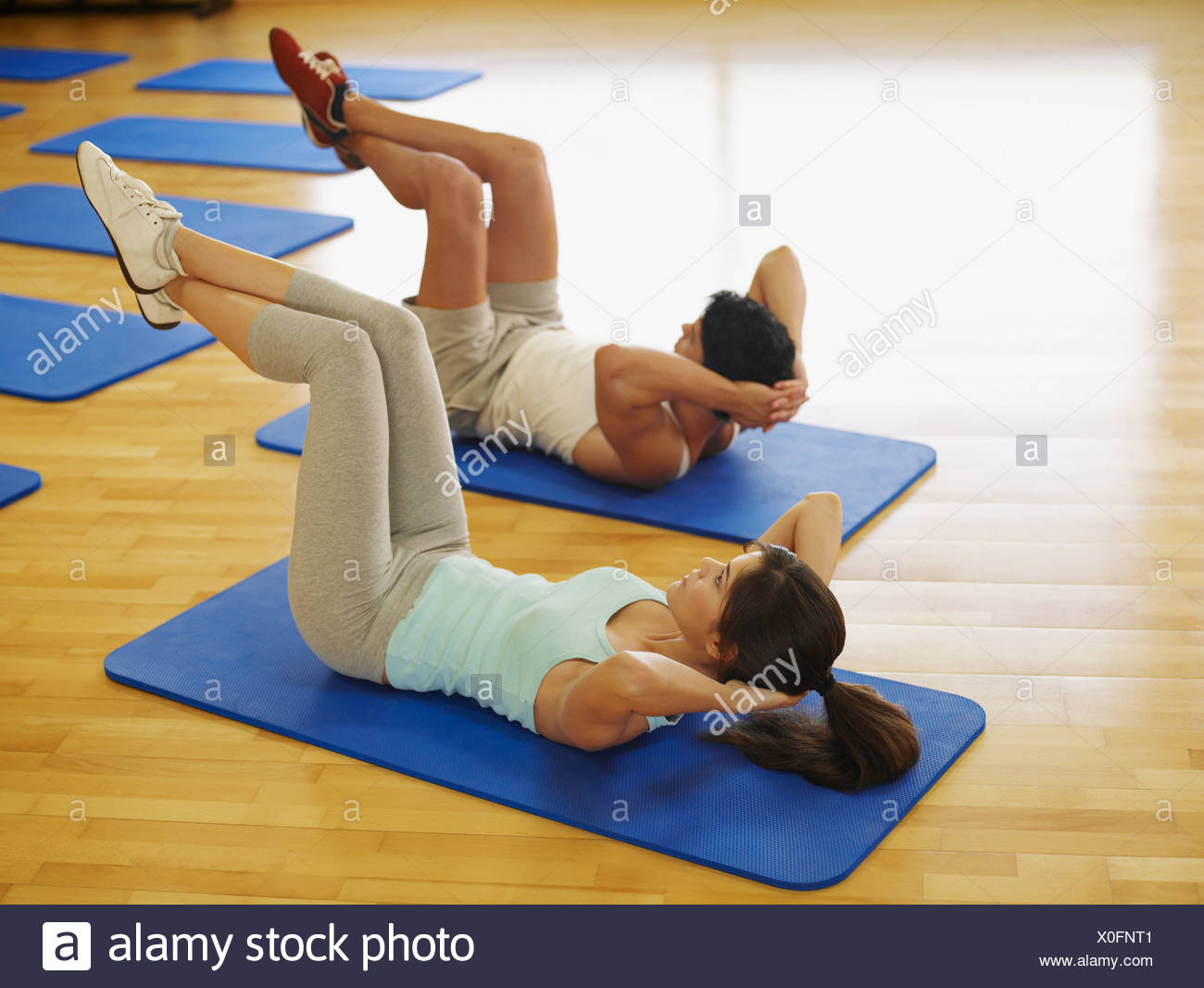 Couple doing mat exercises in a fitness studio - Stock Image