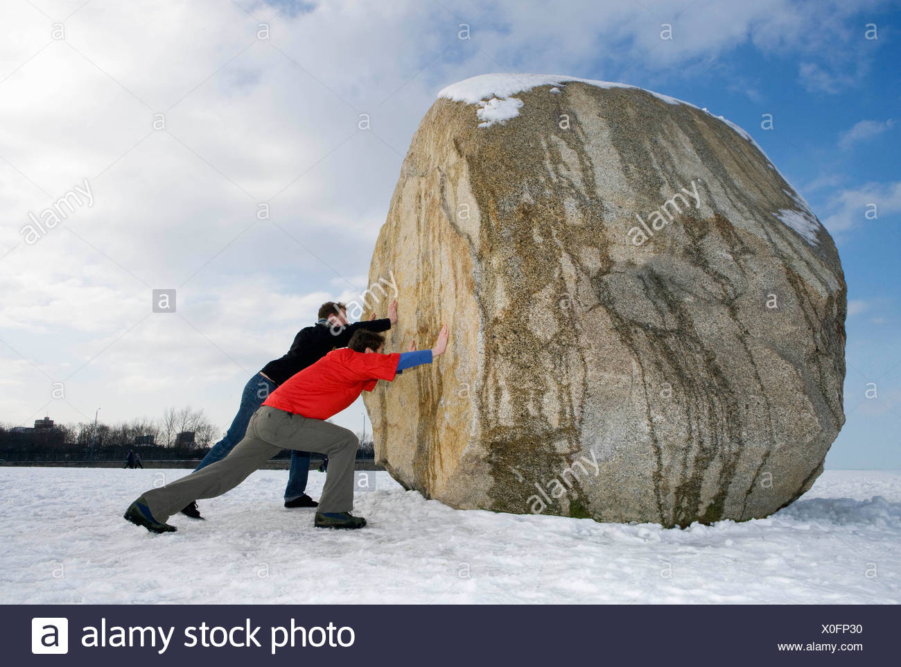 2 men pushing massive boulder - Stock Image