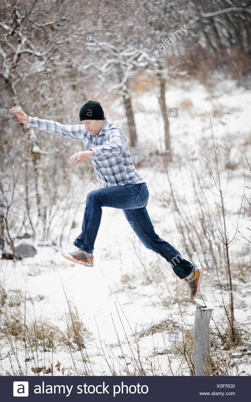 A man leaping from one post to another in the snowy woodland. - Stock Image
