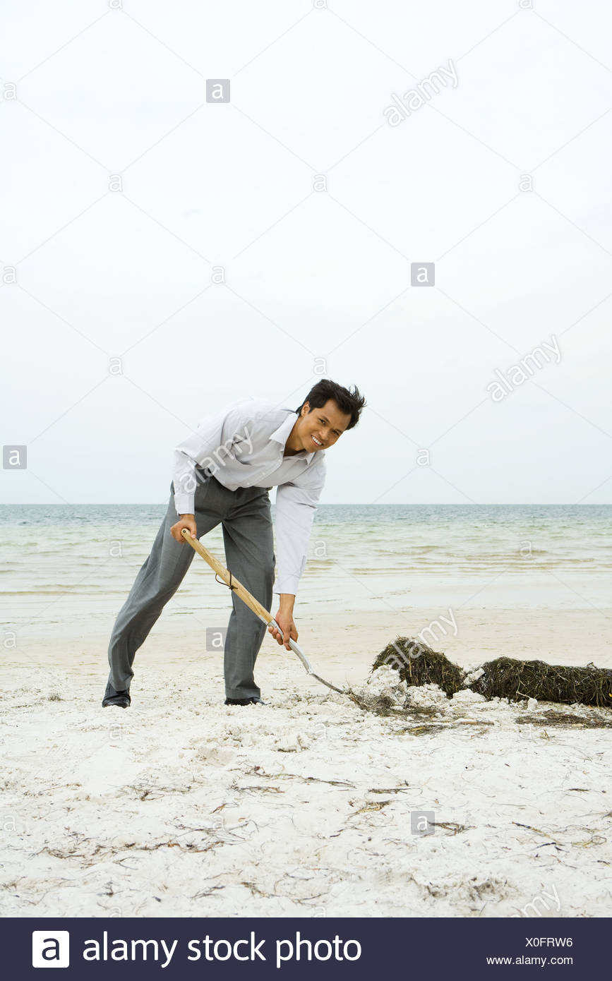 Man at the beach scooping sand with shovel, smiling at camera, full length Stock Photo