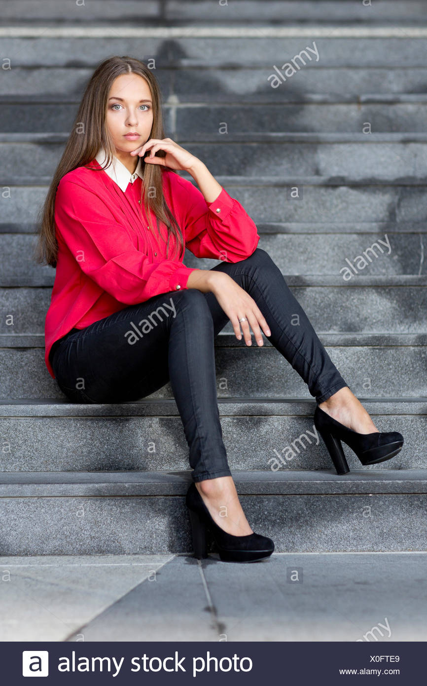 8ee0b50be2c8d4 Young woman wearing a red top, black trousers and high black shoes posing  while sitting on stairs