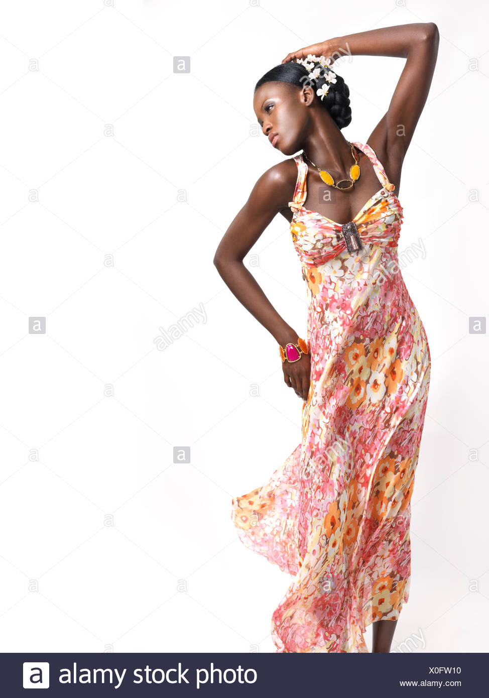 0a2e75f78f81 Beautiful young african american woman wearing a flying pink floral summer dress  isolated on white background