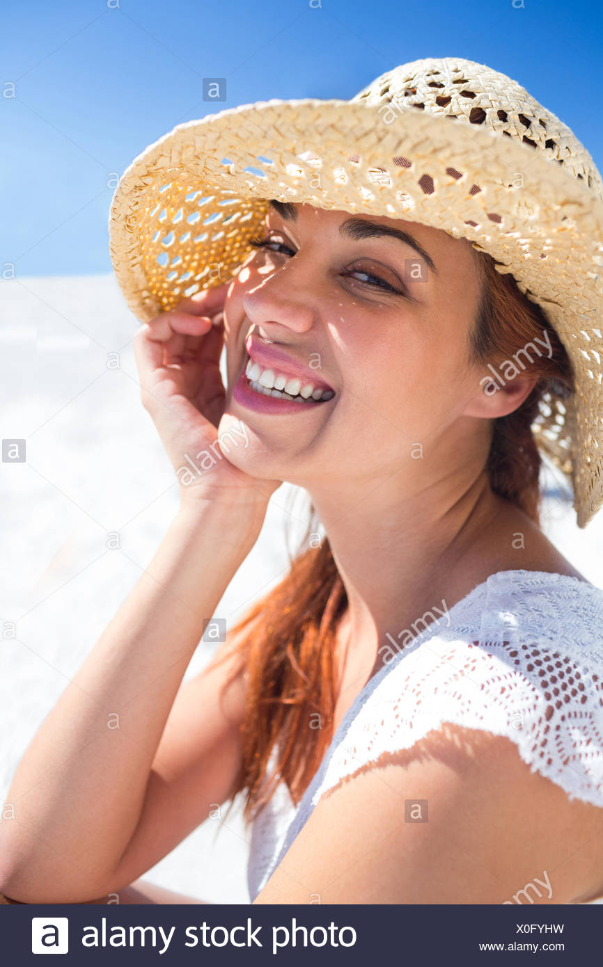 Pretty brunette wearing straw hat and looking at camera - Stock Image