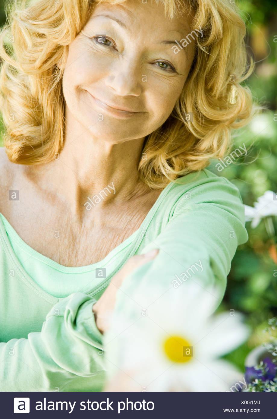 Senior woman holding out flower, portrait Stock Photo