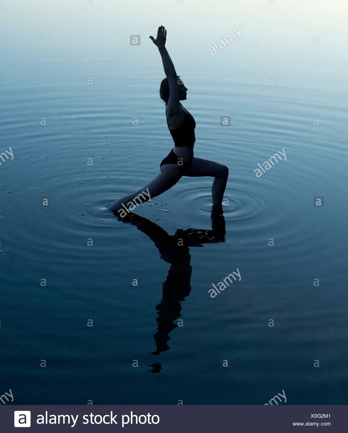 Woman in yoga pose in lake Stock Photo