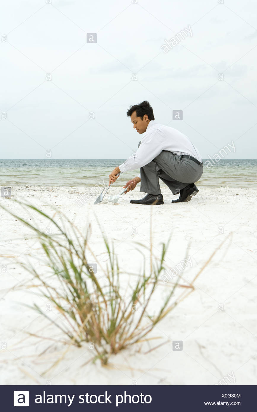 Man crouching on beach, sweeping sand into dustpan, side view - Stock Image