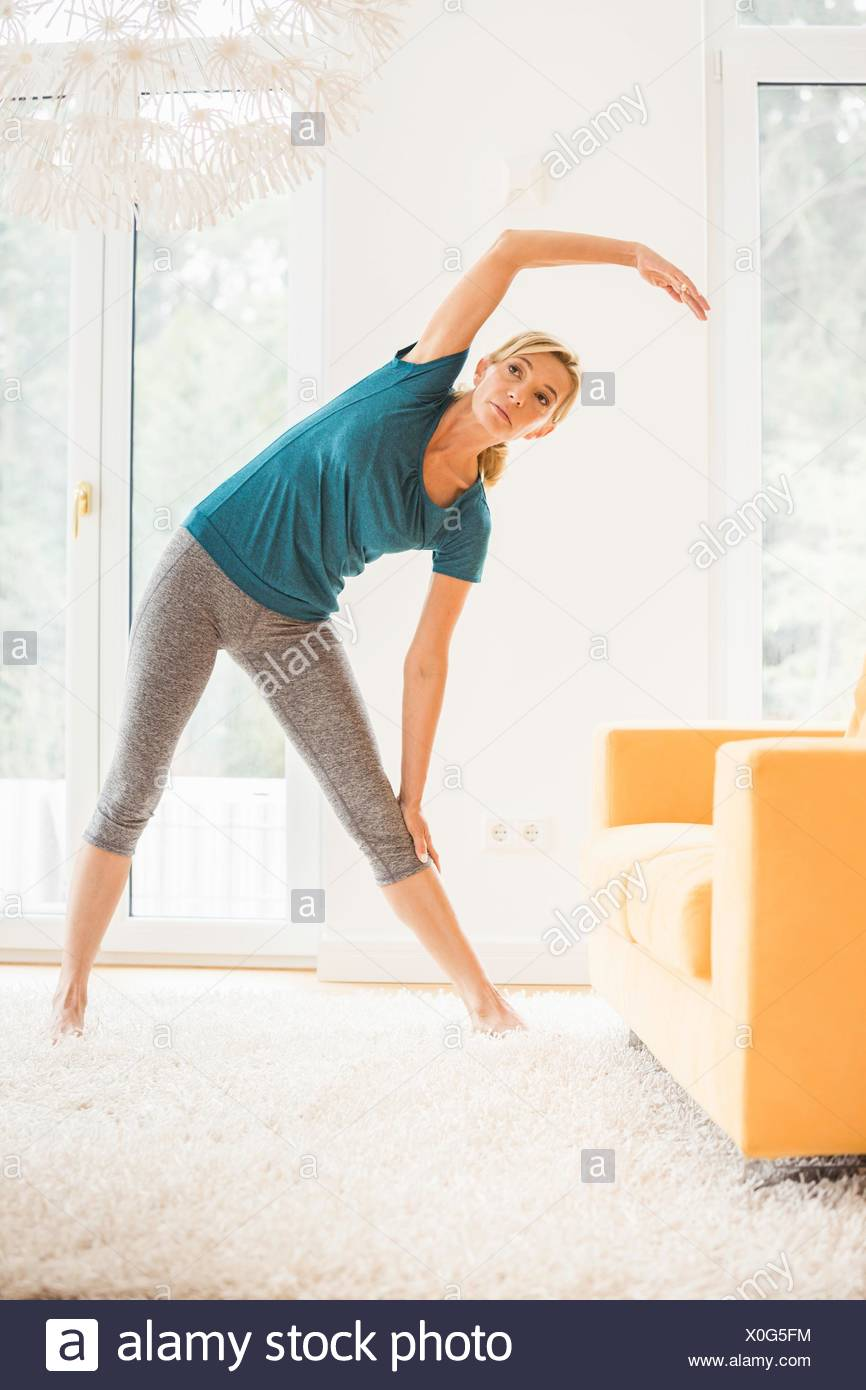 Mature woman bending over sideways whilst exercising in living room - Stock Image