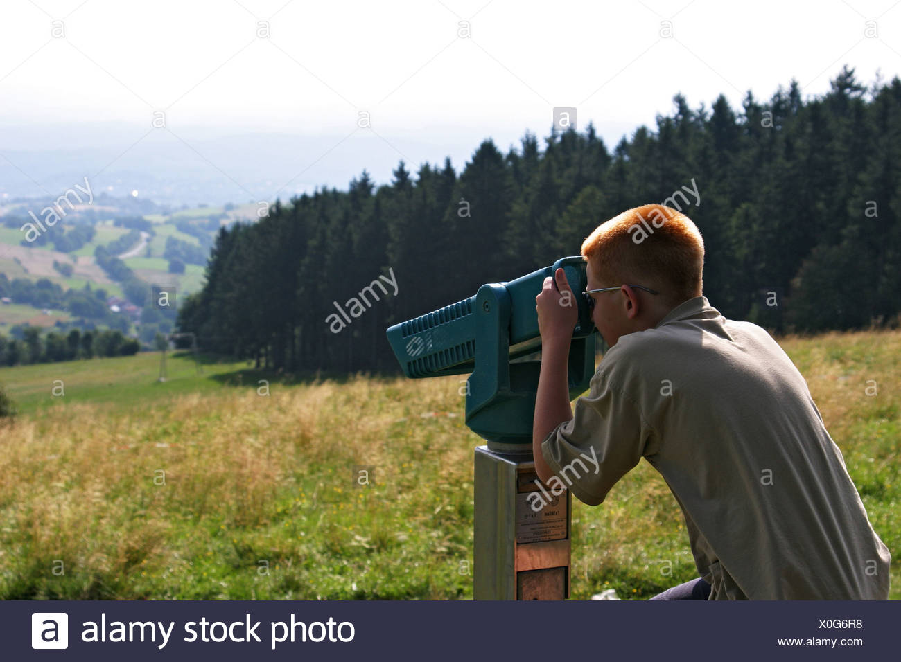 Boy with short cut red hair looking through a fixly mounted telescope. Hoherodskopf mountain, Vogelsberg, Hesse, Germany. Stock Photo