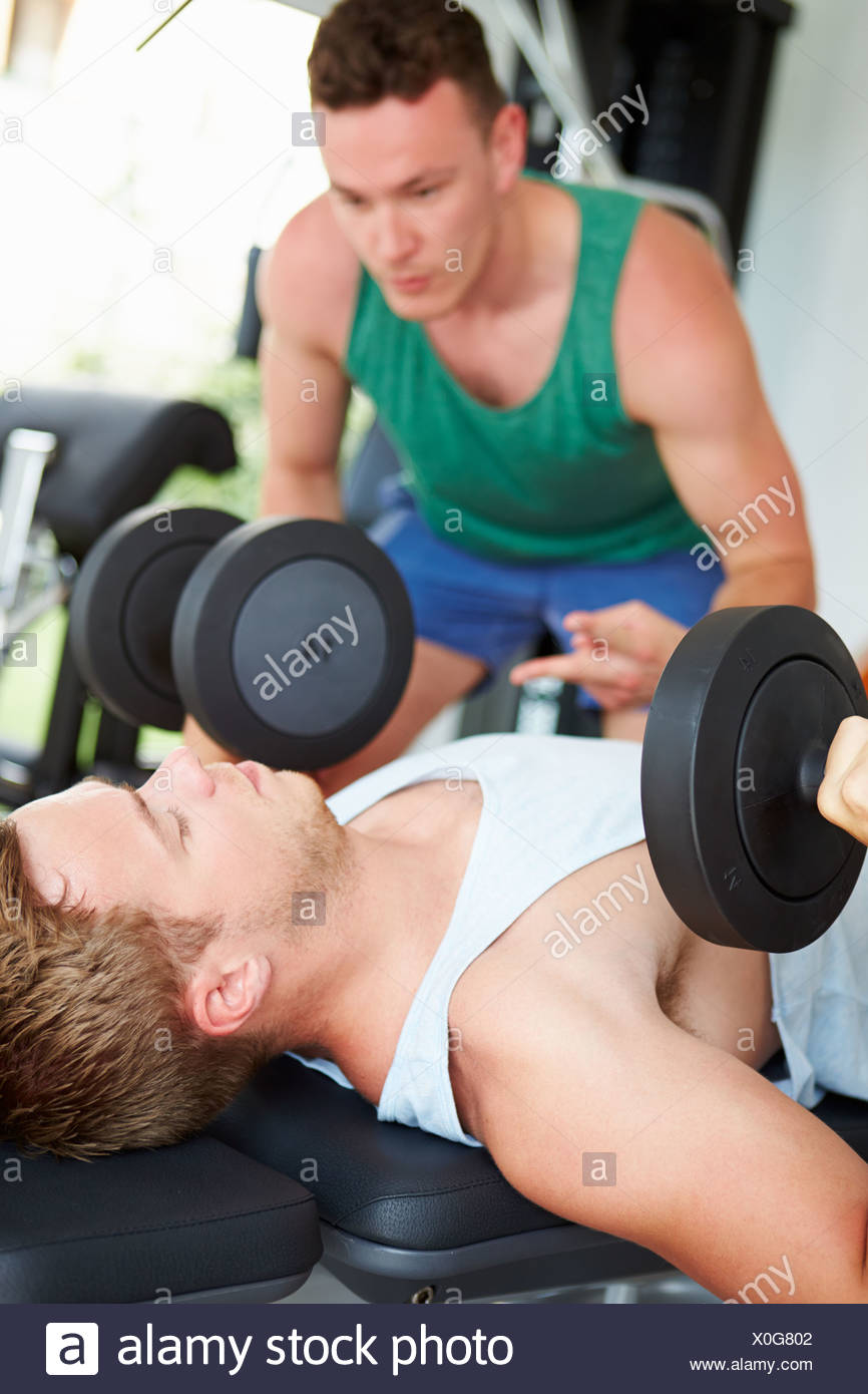 Two Young Men Training In Gym With Weights - Stock Image