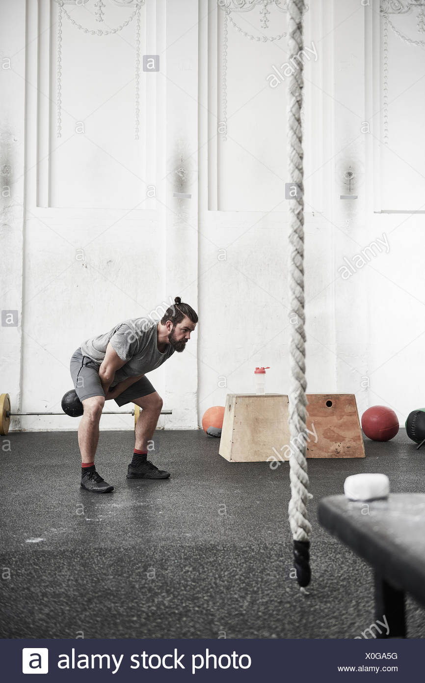 Man working out with kettlebell in cross training gym - Stock Image