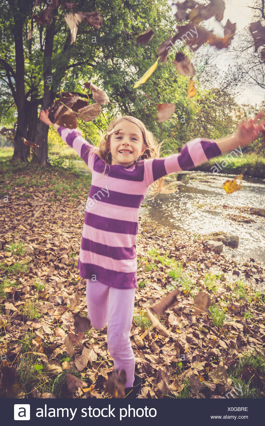 Little girl throwing autumn leaves - Stock Image