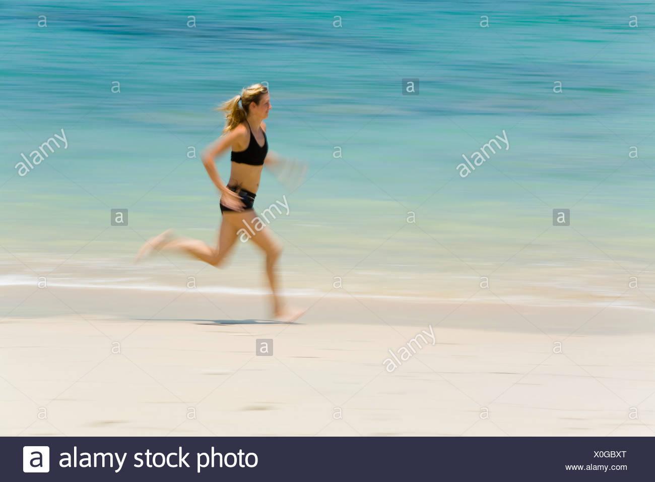 A Woman Tourist Runs Along The Beach On A Tropical Island; Koh Lanta,Thailand Stock Photo