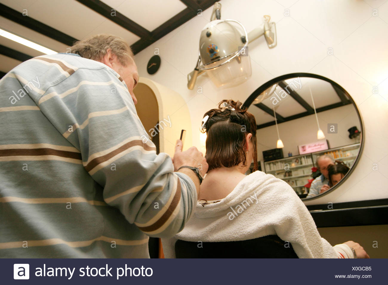hairdresser cutting the hairs of a woman - Stock Image