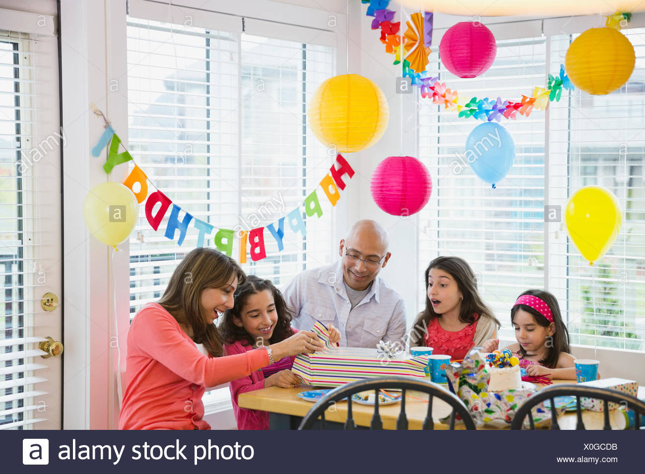 Little girl and mother opening gift as family watches - Stock Image