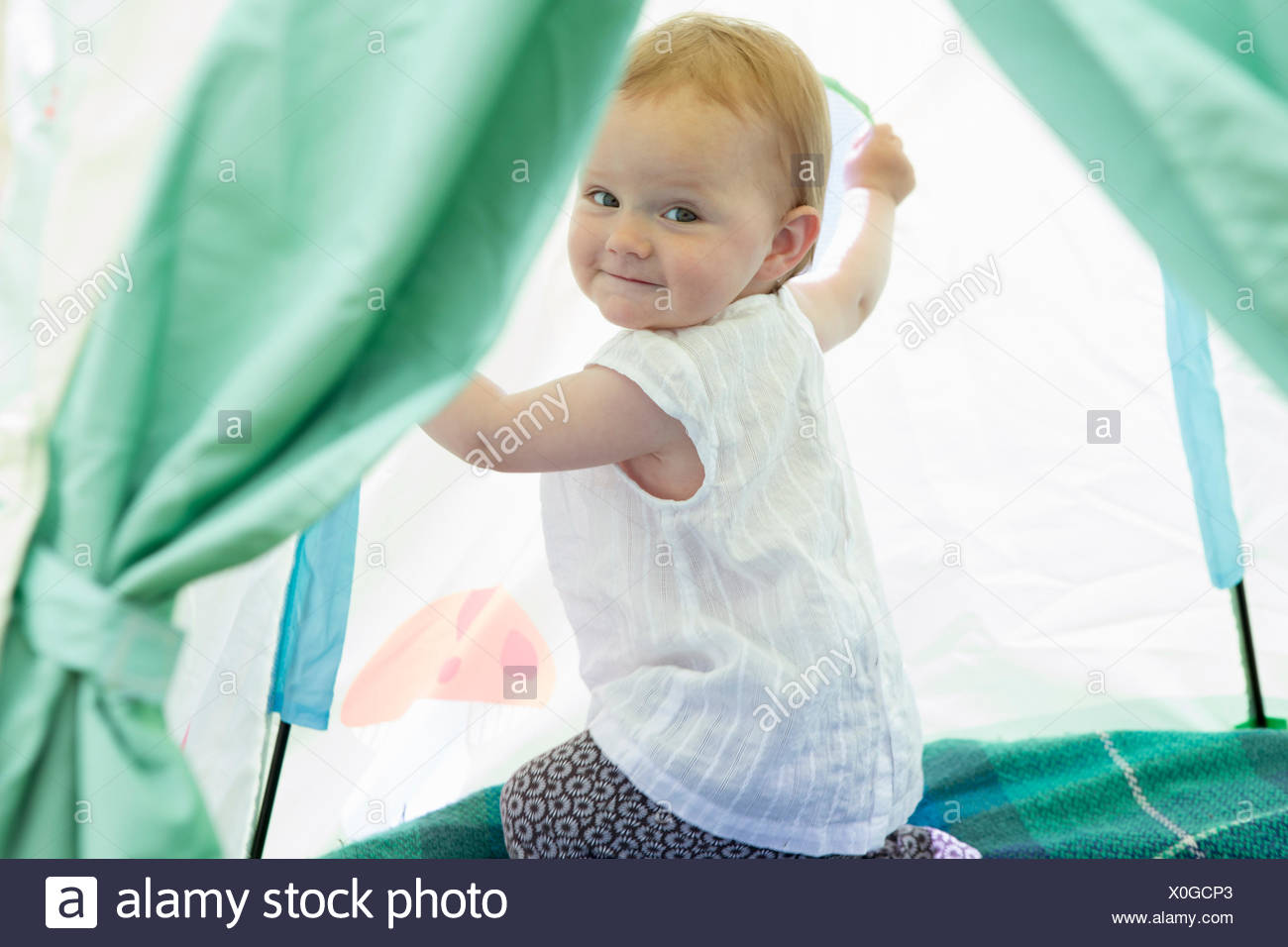 Baby girl playing in tent - Stock Image