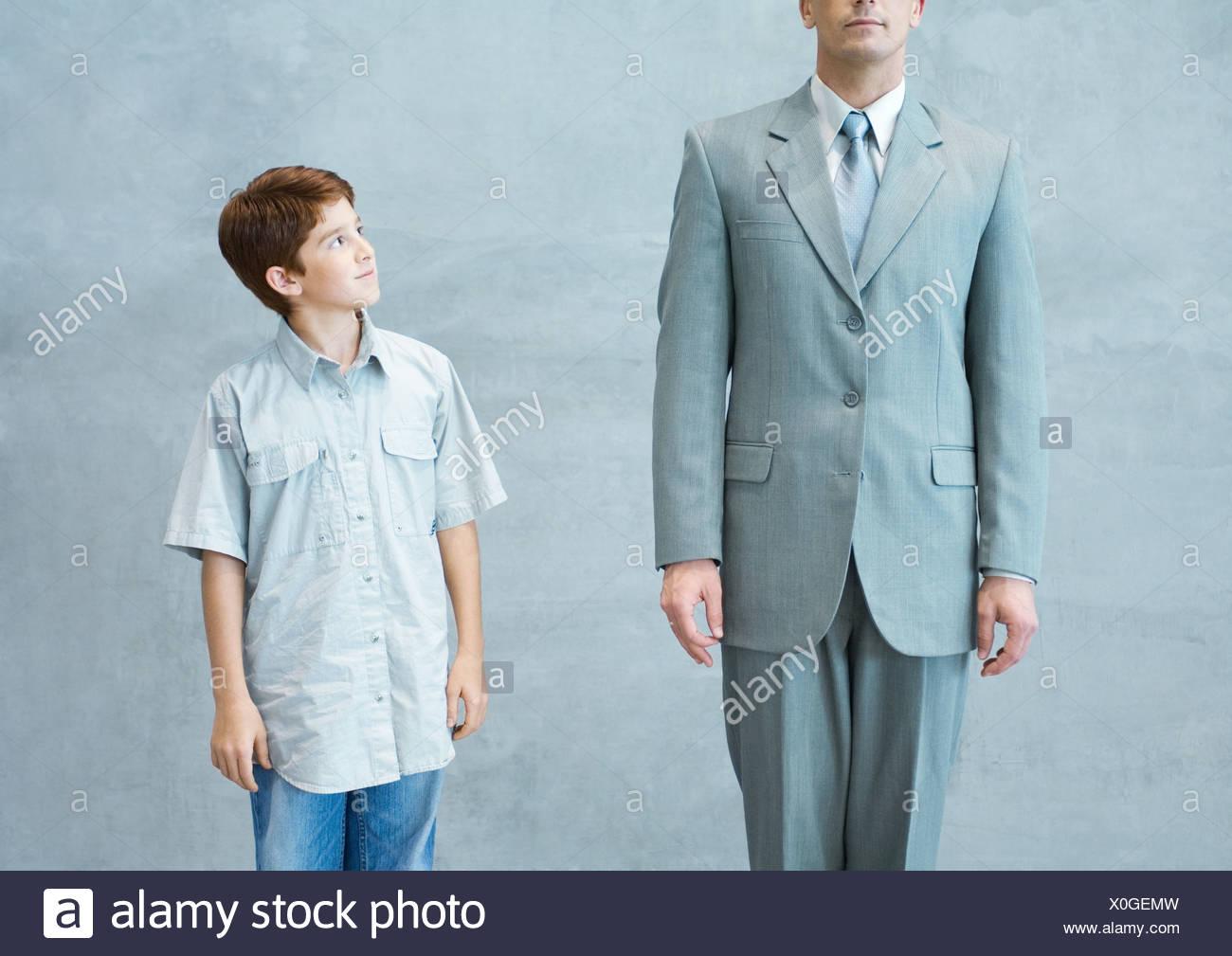 Boy looking up admiringly at businessman - Stock Image