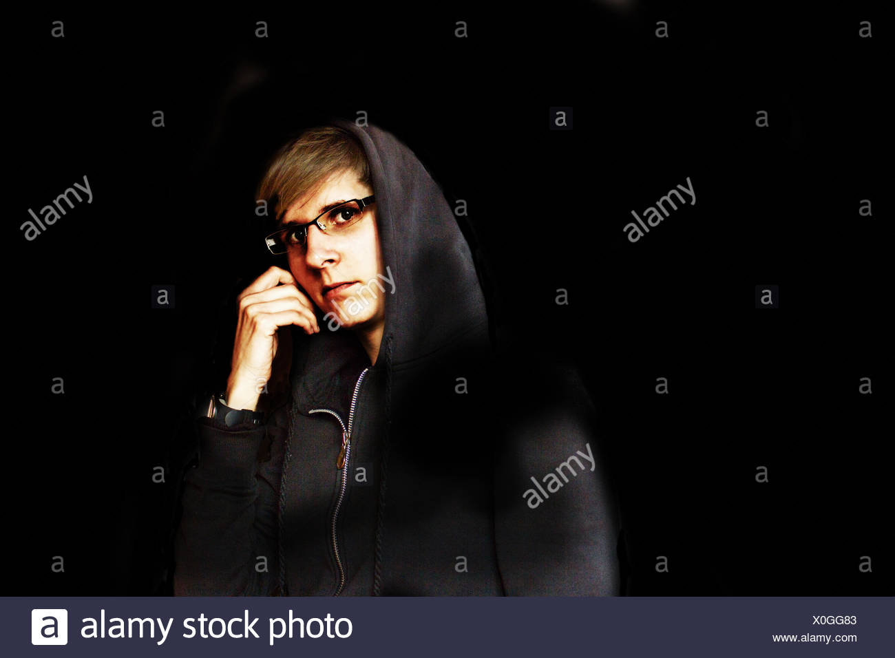Young woman in sweat jacket with hood in the dark - Stock Image