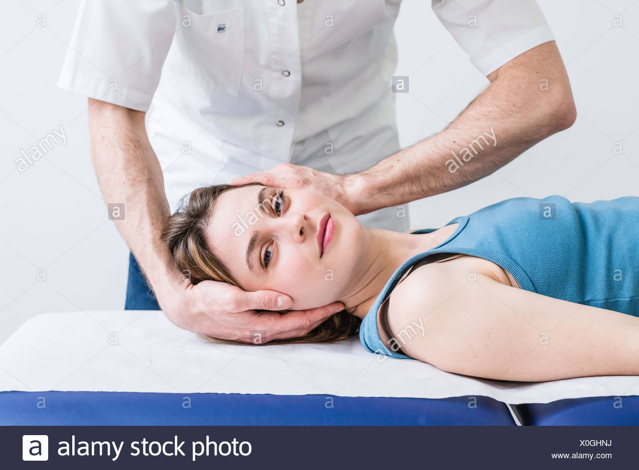Structural osteopathy session in a woman suffering from neck pain. - Stock Image