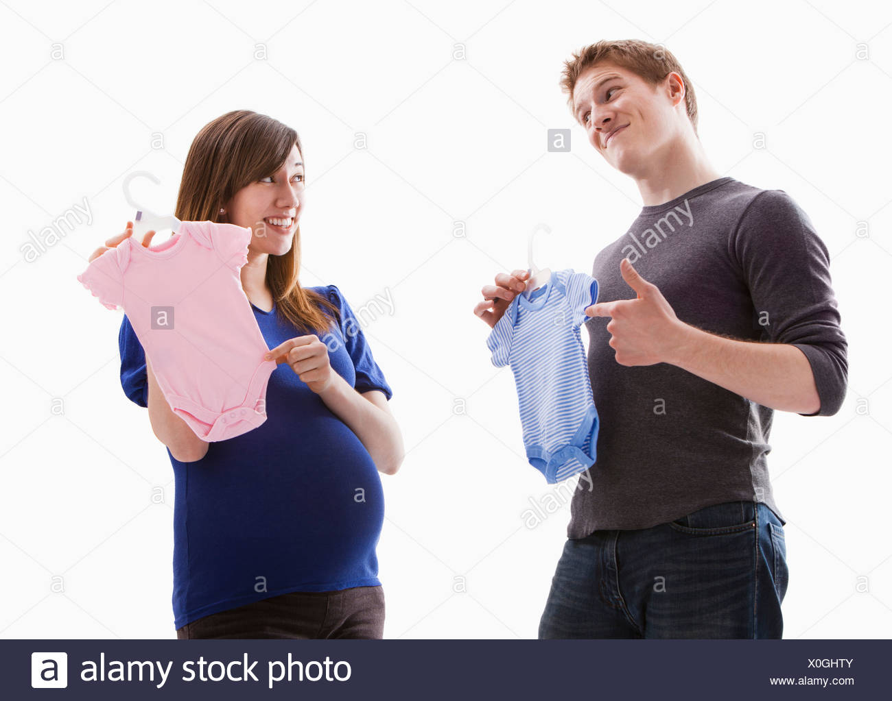 Studio Shot of young couple holding onesie Stock Photo