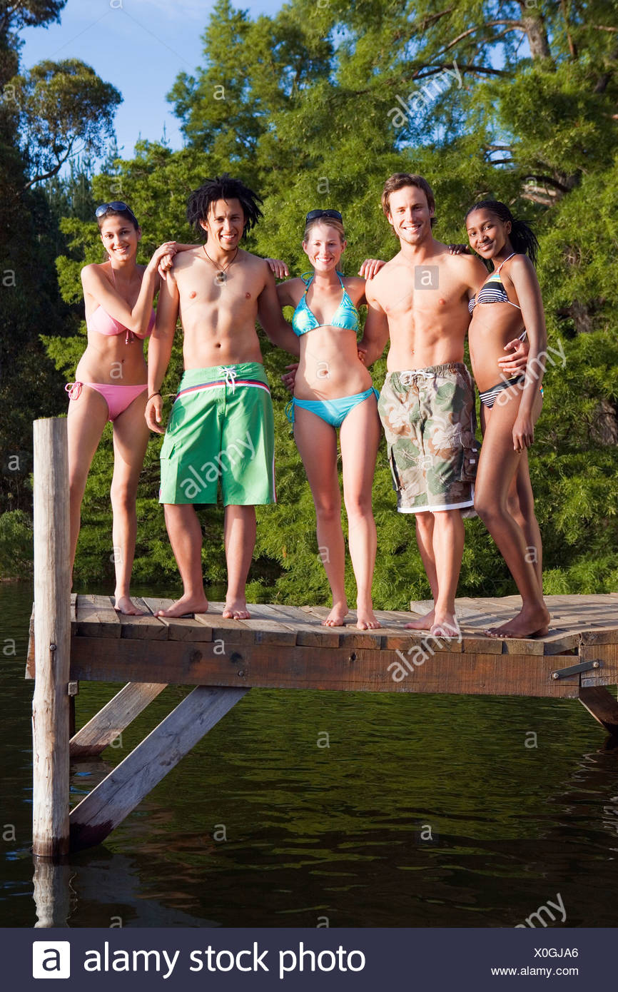 Five young adults in swimwear standing side by side on lake jetty smiling front view portrait - Stock Image