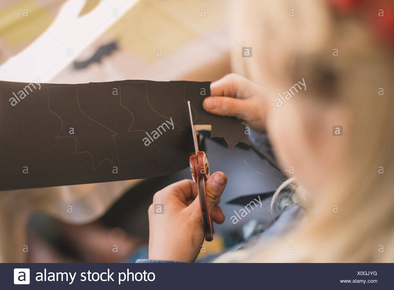 Girl cutting paper with owl-shape scissors - Stock Image