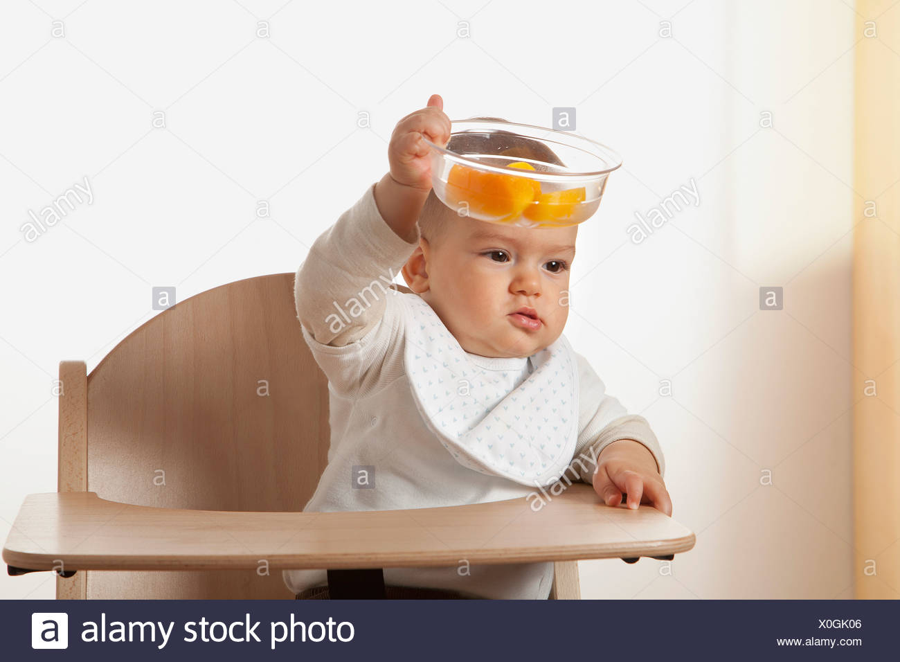 portrait of baby in high chair holding bowl with fruit Stock Photo