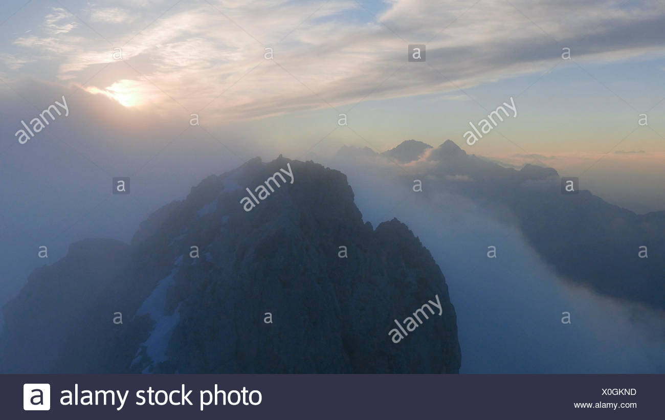 Sundown and diffuse light and fog, view of Schüsselkarspitze on rock Storm of the west ridge in Wetterstein Range, behind it Mieminger mountains with Hohe Wand and Hochplattig and Mitterspitzen - Stock Image