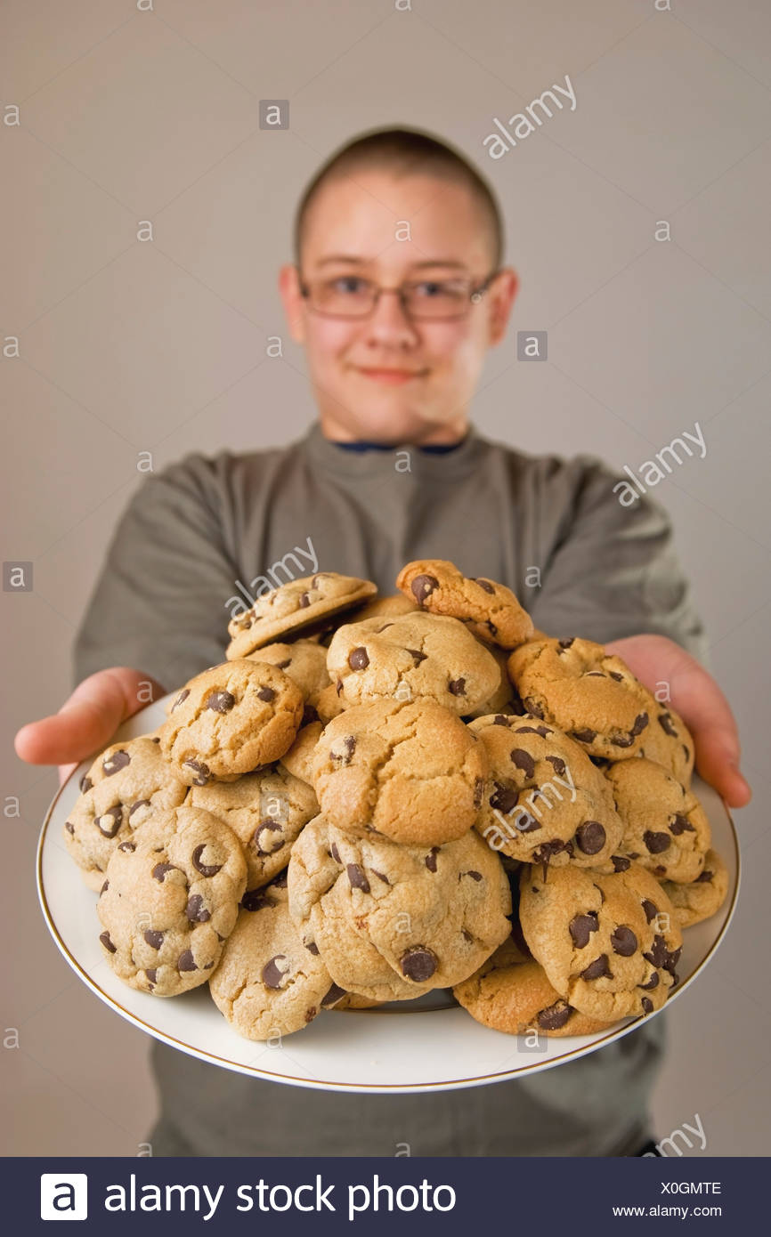 A Boy Holding A Plate Of Chocolate Chip Cookies Stock Photo