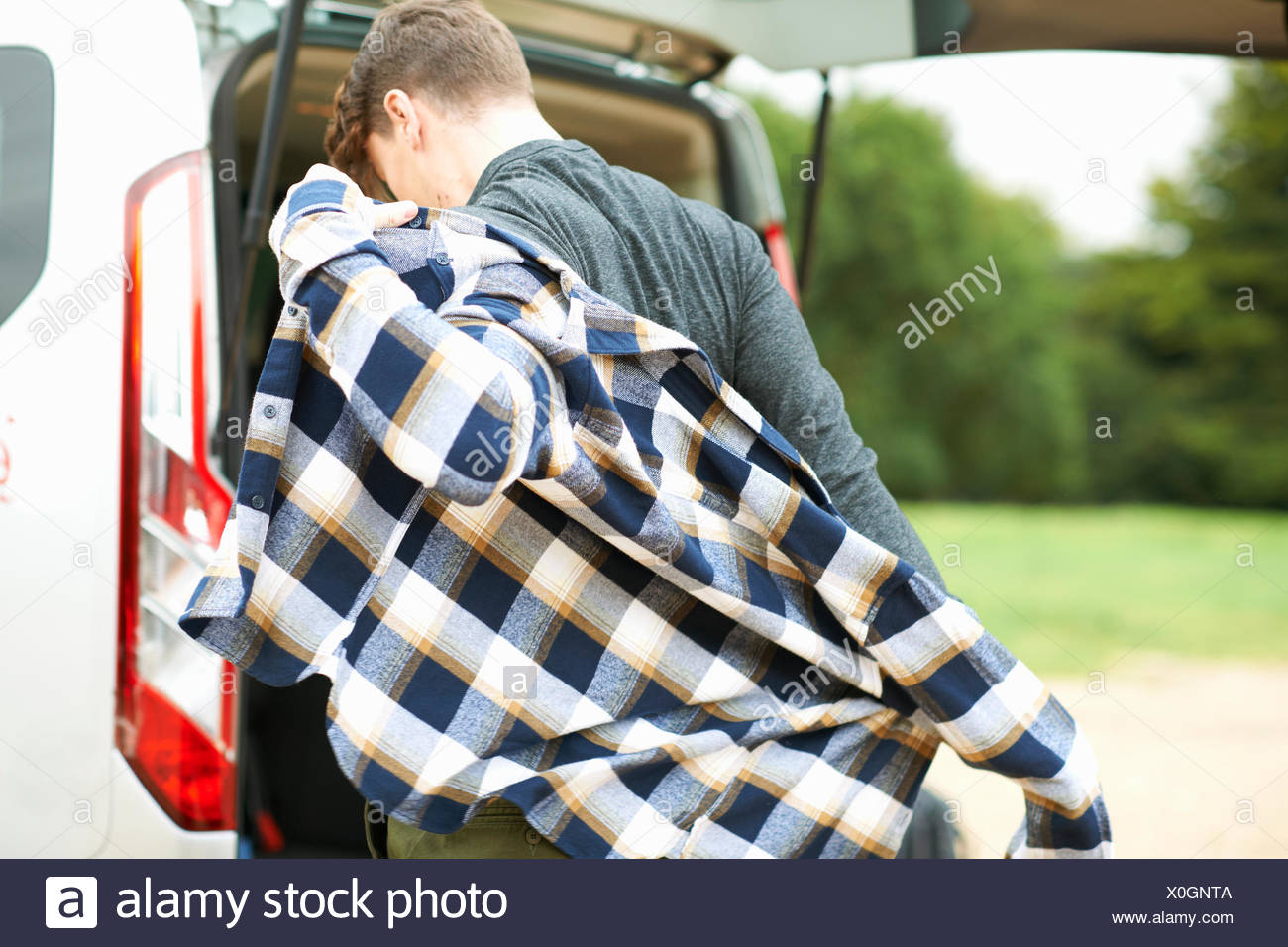 Rear view of man by automobile boot putting on plaid shirt - Stock Image