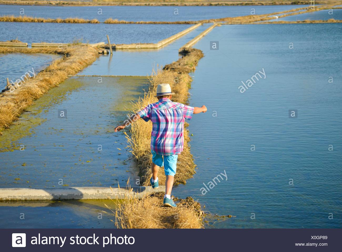 Happy boy jumping ditches rice fields, Albufera in Valencia, Spain, Europe Stock Photo
