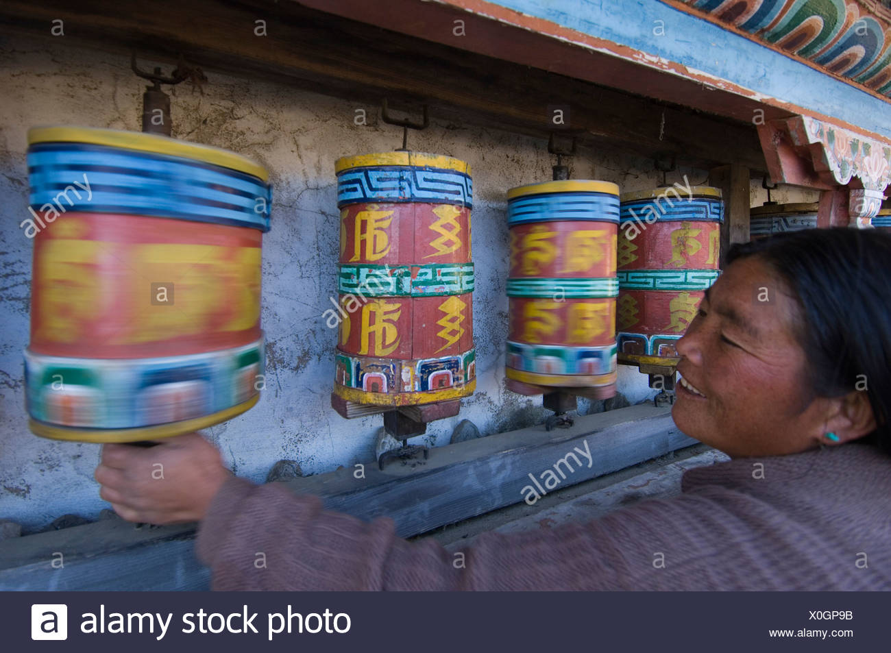 Woman using prayermill in Galdan Namge Lhatse monastry Tawang - Stock Image