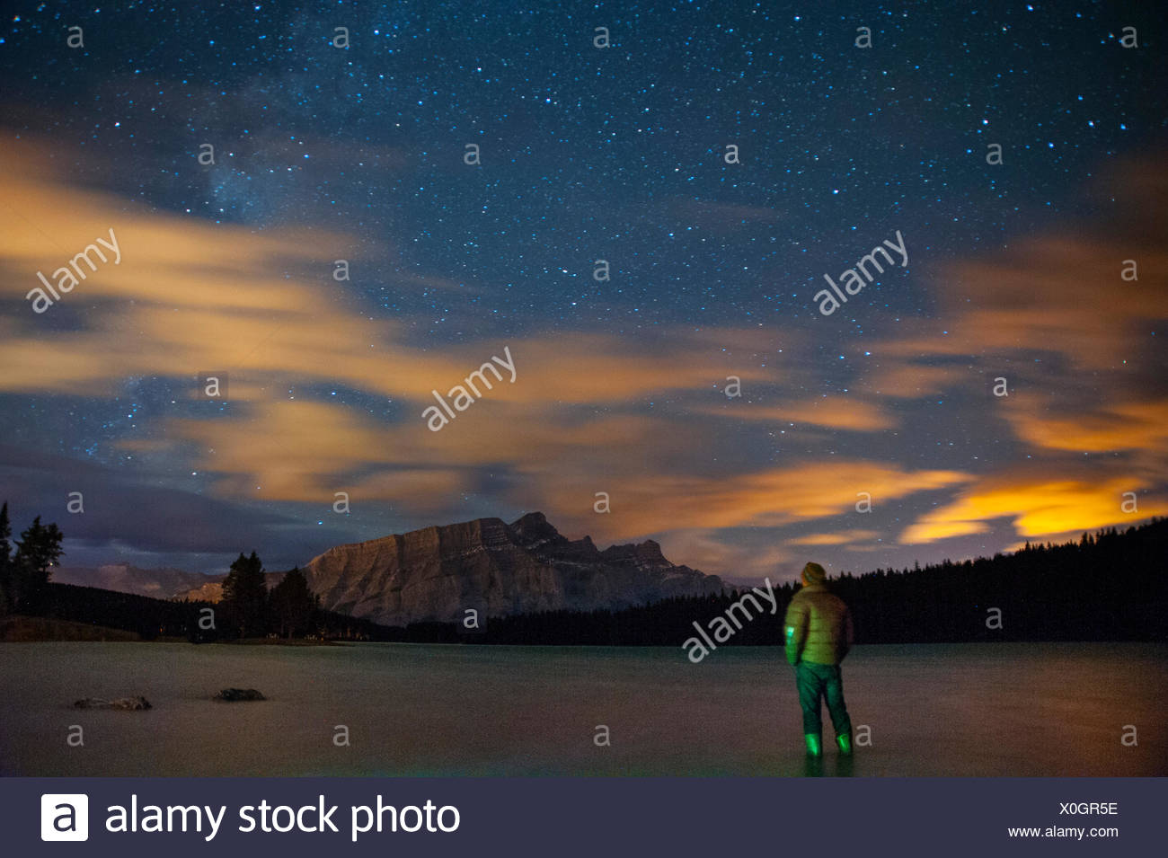 A camper watches he Milky Way soaring over Mount Rundle and Two Jack Lake. - Stock Image