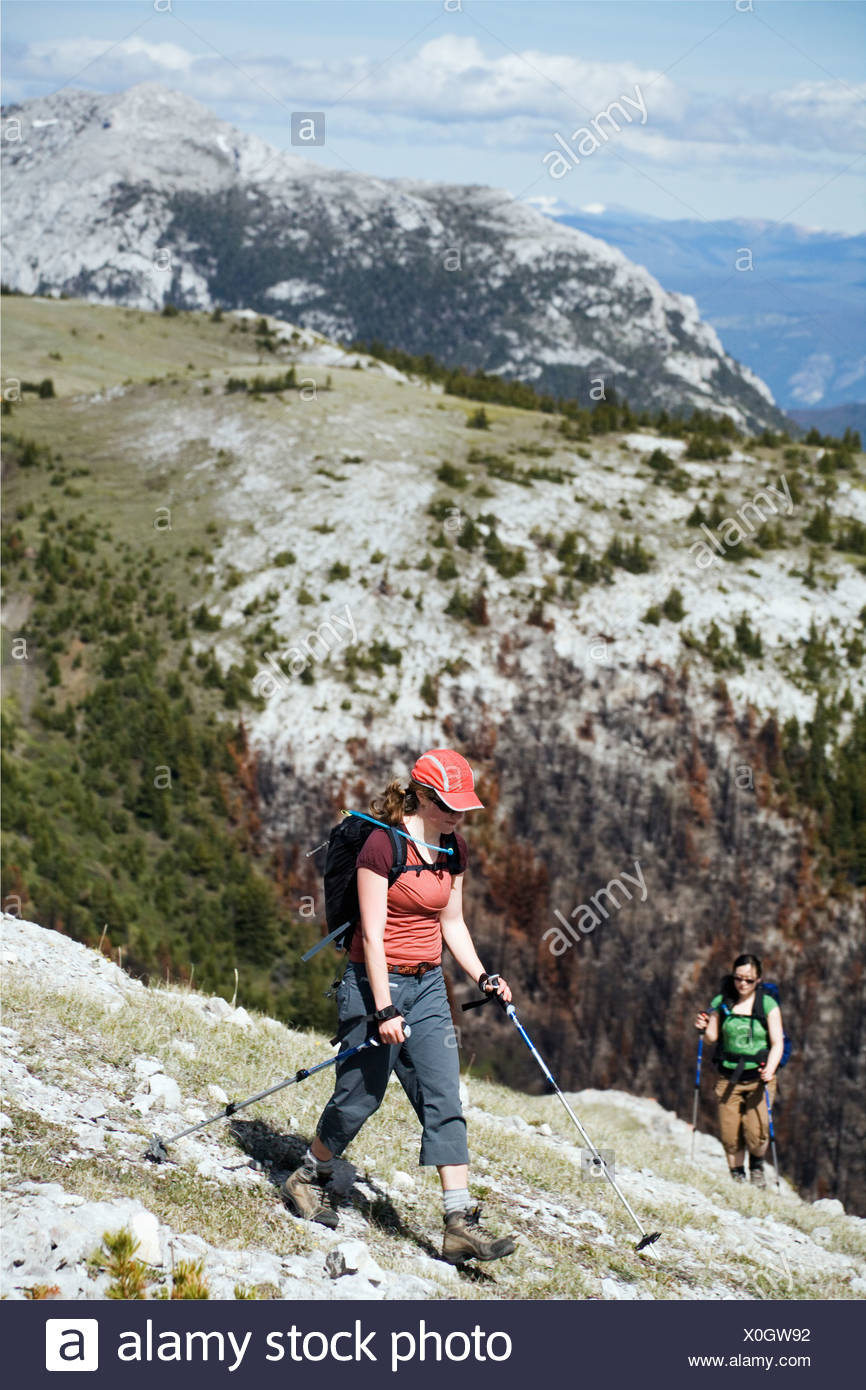 Two women hike on a broad ridge in the southern Chilcotin mountains. - Stock Image