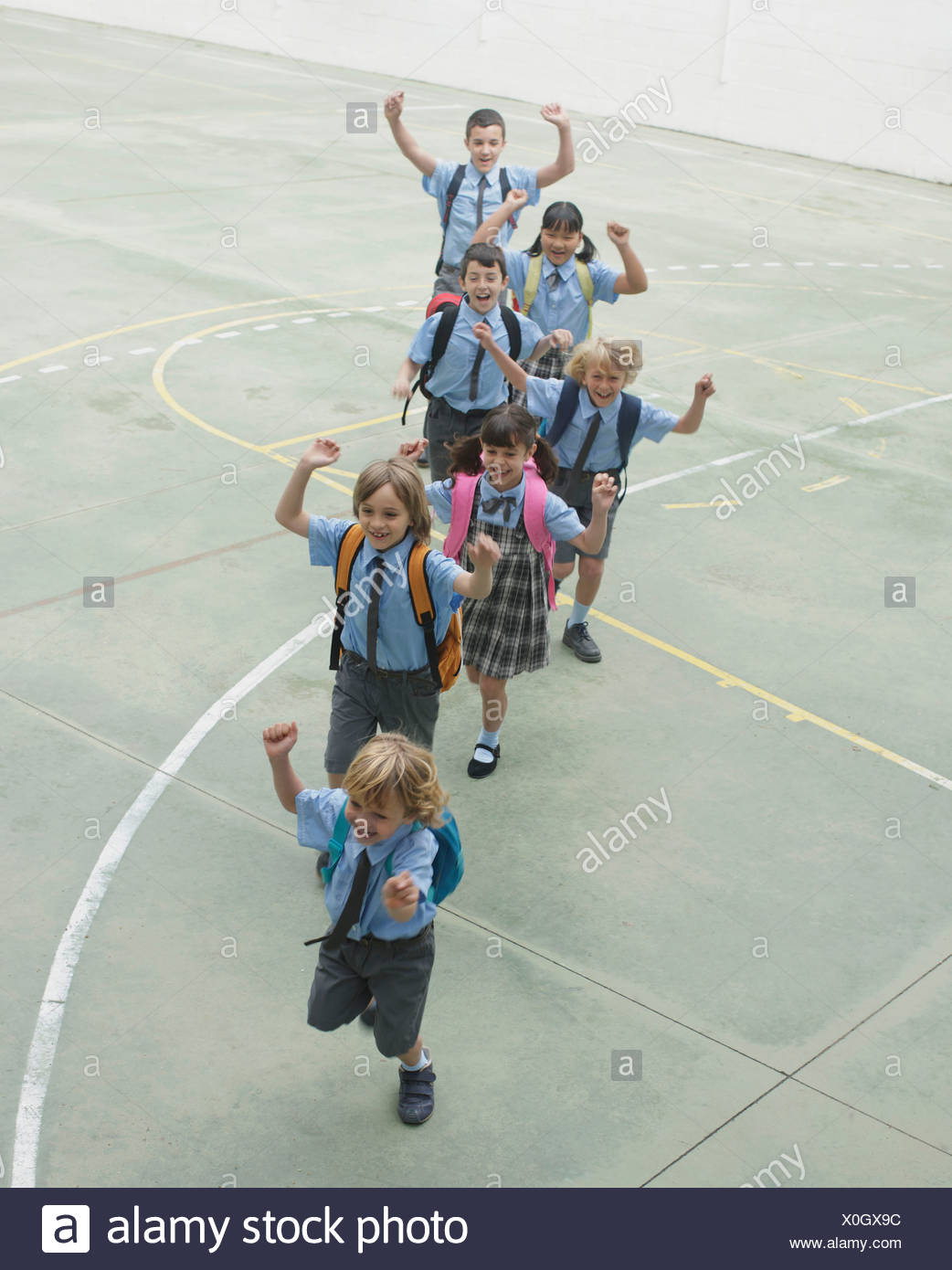 School children running in courtyard - Stock Image