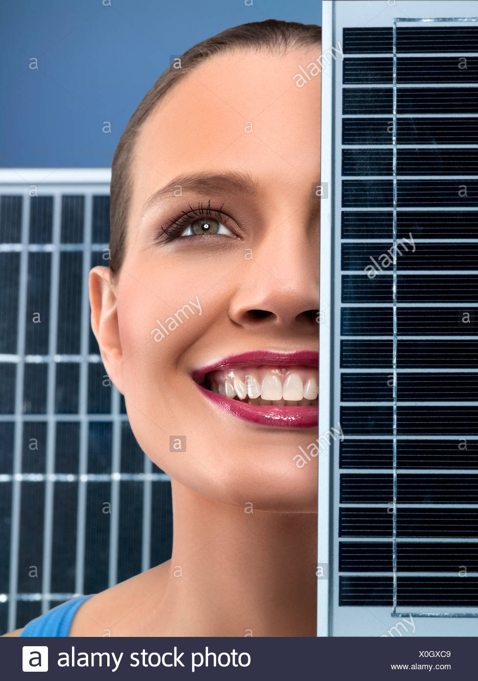Young happy woman near solar panels, studio shot - Stock Image
