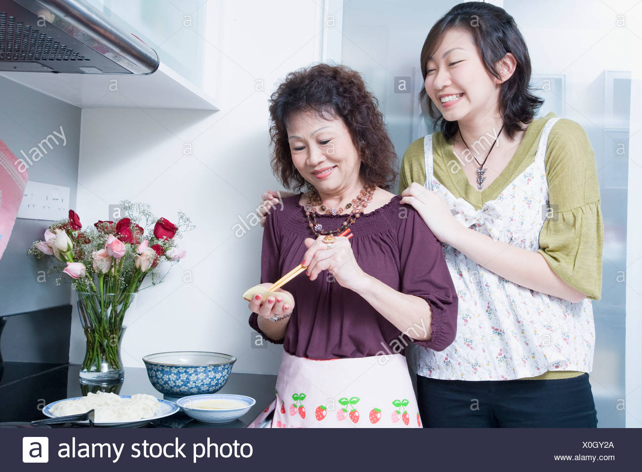 Senior woman preparing food with her granddaughter standing behind her and smiling - Stock Image