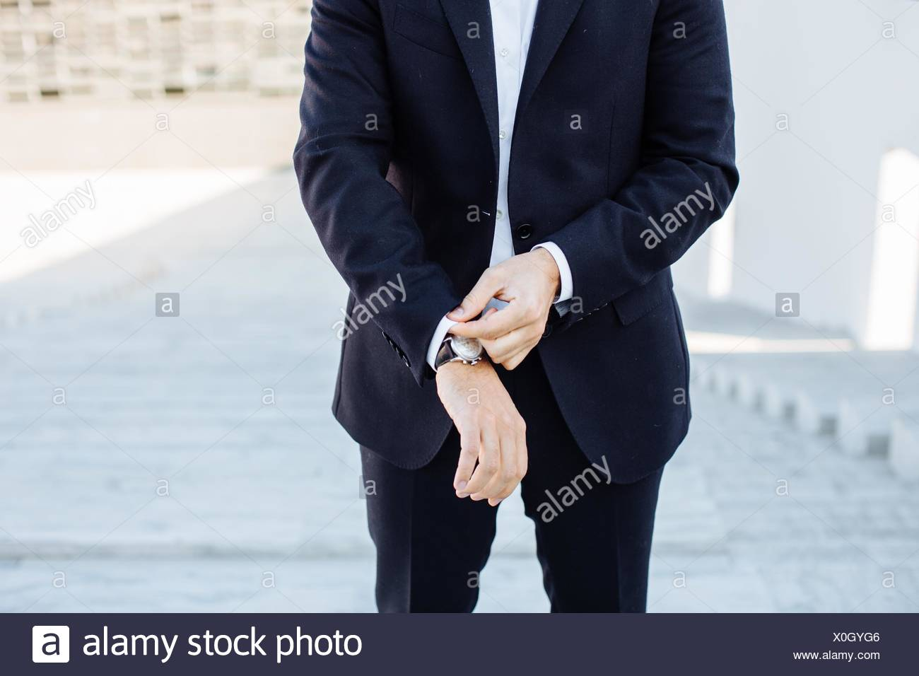 Mature businessman, outdoors, adjusting shirt cuff, mid section - Stock Image