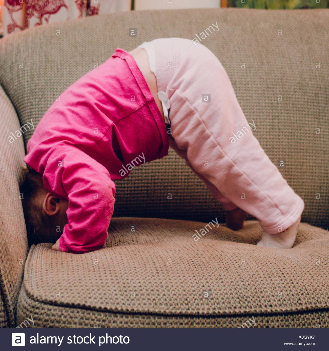 Side View Of Baby Girls Doing Headstand On Sofa At Home - Stock Image